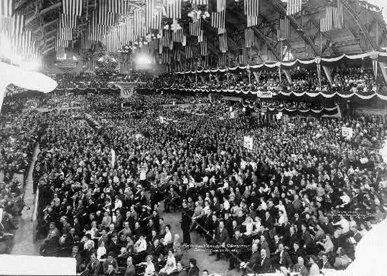 black and white photo of thousands of delegates in a hall hung with flags from the rafters