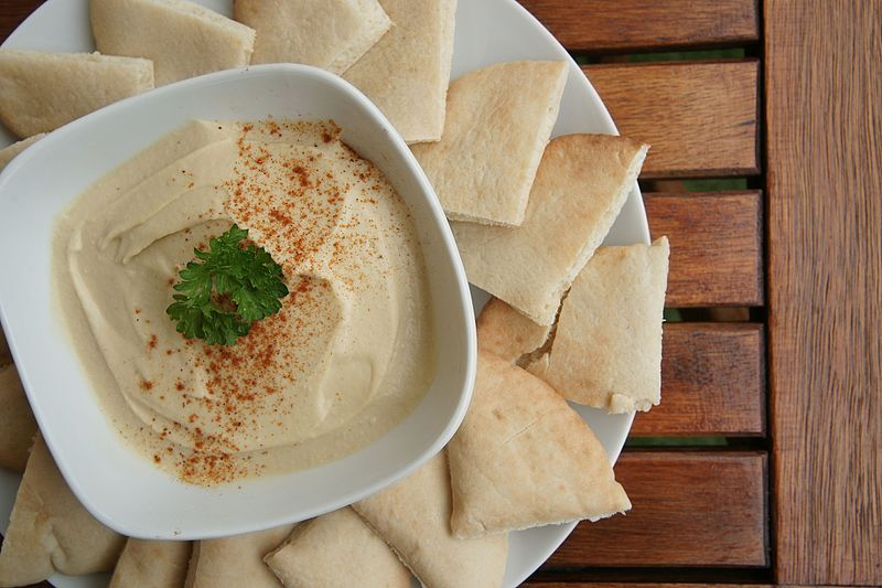 Bowl of hummus and pita bread on a plate