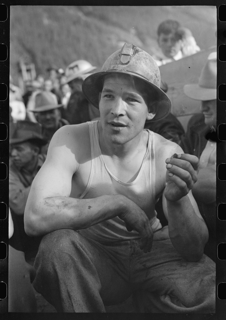 black and white photo of a young man wearing a hard hat and sleeveless undershirt