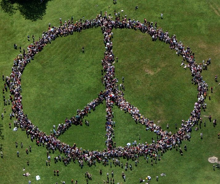 People on a field standing in the shape of a peace sign, photographed from above.