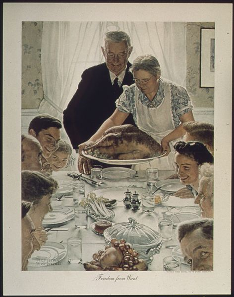 Painting of table surrounded by smiling and talking people and set for dinner; a woman settting a roast turkey at the head with a man in a suit behind her.