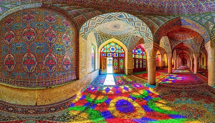 Interior photo of intricately tiled walls and ceiling lit by stained glass window.